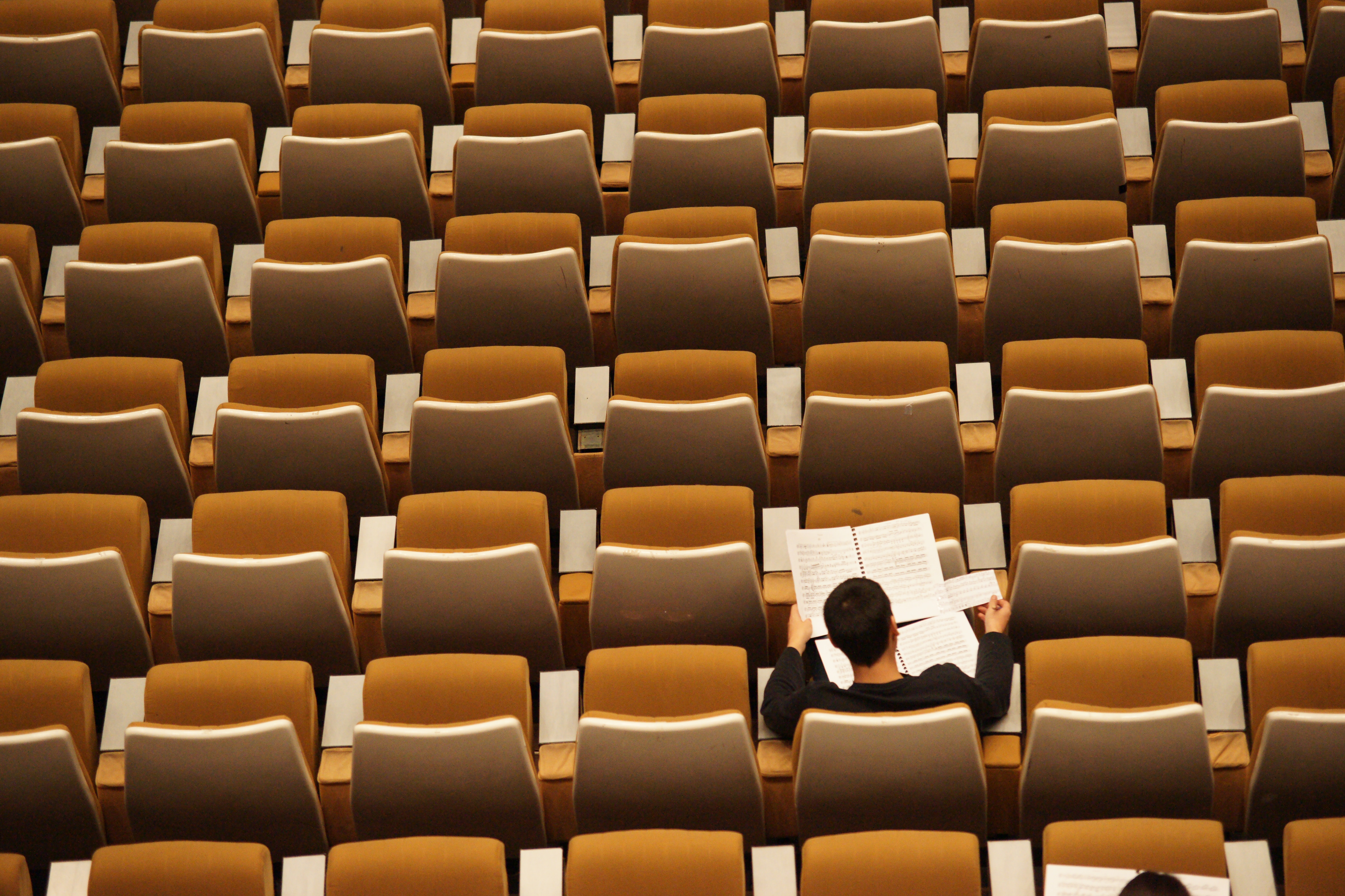 photo os a man in an auditorium reading a paper